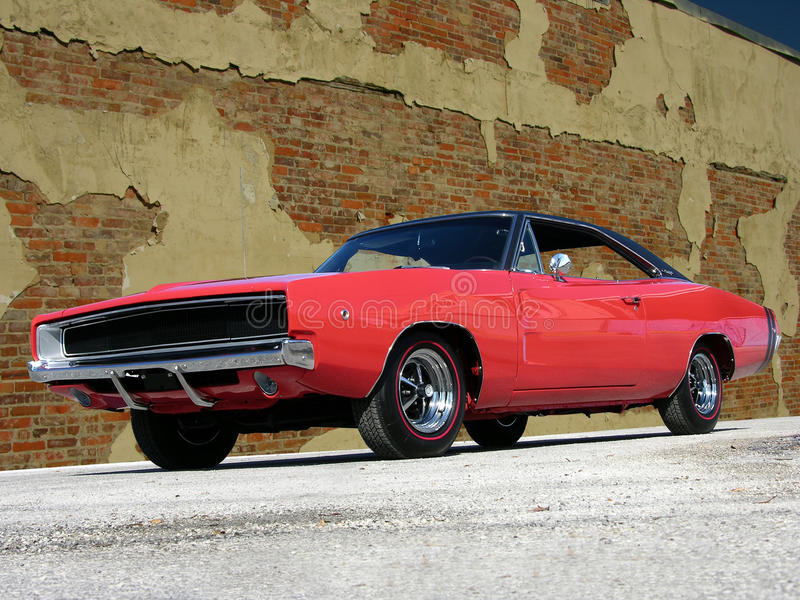 1968 Dodge Charger RT. In red with black vinyl top. Hide away headlights sitting next to a brick wall. Mopar heritage stock image