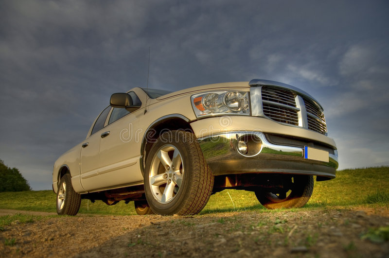 Dodge ram pickup sideview. A white colored pickup in beautiful landscape from the back as a hdr image royalty free stock images