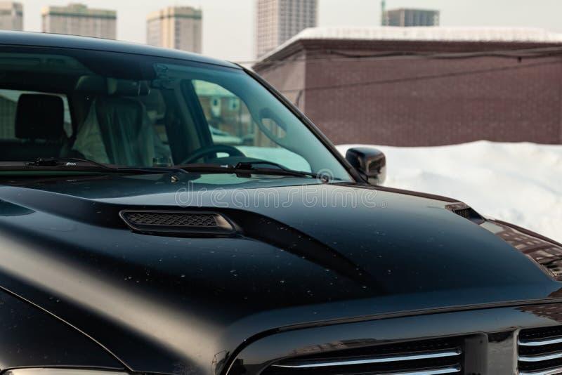 Dodge Ram preto com um motor de 5 7 litros de capa com opinião de furos de ventilação no carro que estaciona com fundo da neve fotos de stock royalty free
