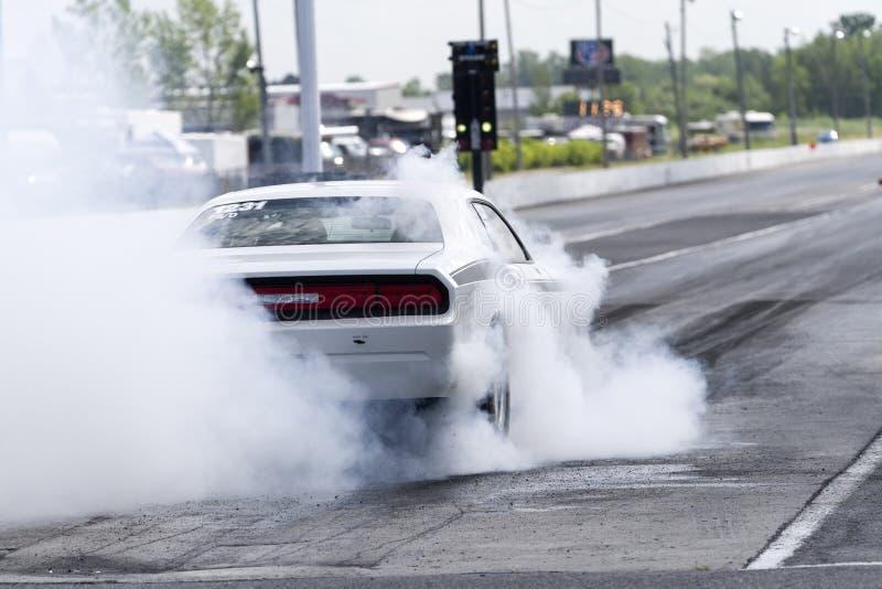 Dodge-uitdager die een rook maken op het rasspoor bij de beginnende lijn tonen royalty-vrije stock afbeelding