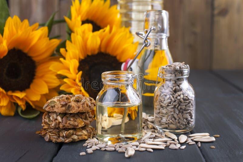 Dodsolnechnoe-Öl in einer Flasche von einem großen und ein klein, ein Blumenstrauß von Sonnenblumenblumen, auf einem deryl Hinter stockfoto