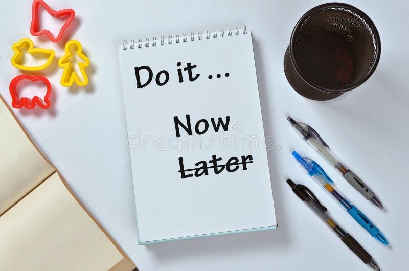 Doe het nu niet recentere tekst op blocnote met bureautoebehoren Bedrijfsmotivatie, inspiratieconcepten stock afbeelding