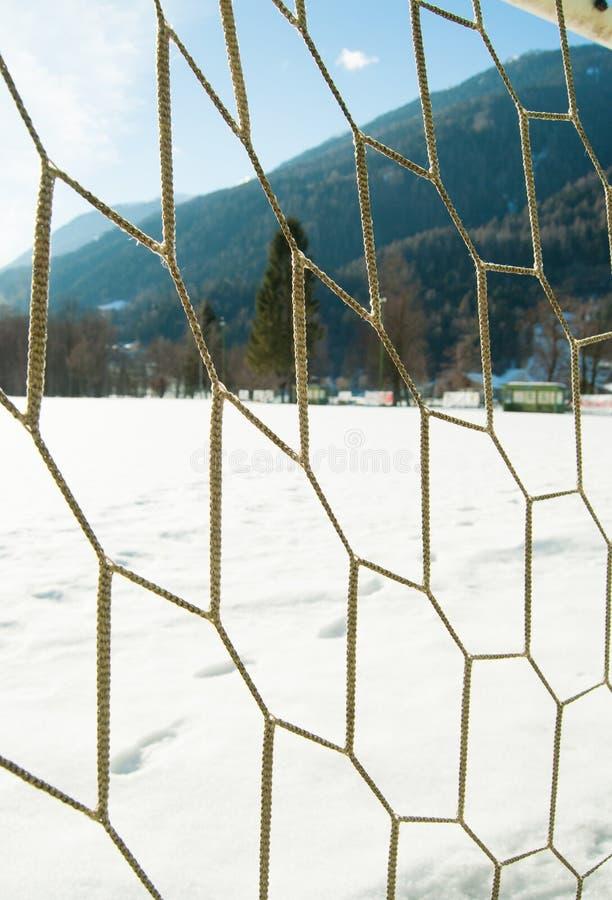 Doel netto van een voetbalgebied met sneeuw en mening over het bosrijke onderstel royalty-vrije stock foto's