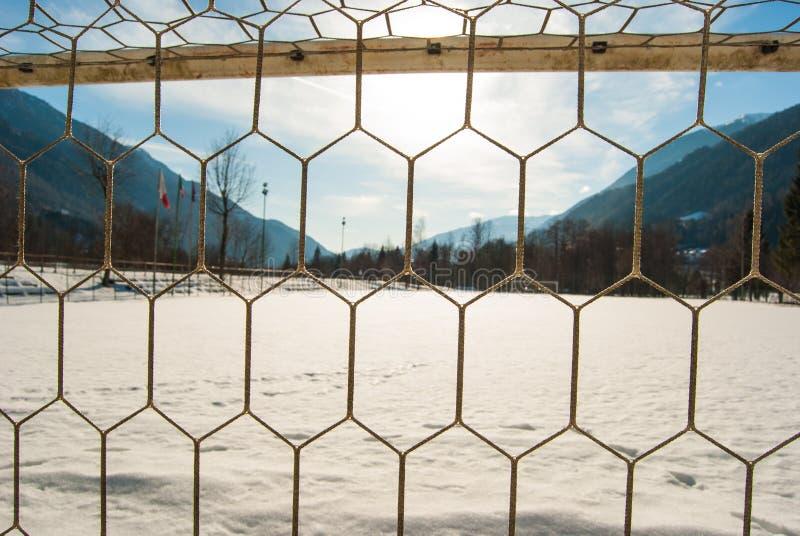 Doel netto van een voetbalgebied met sneeuw en panorama op mountai stock afbeeldingen