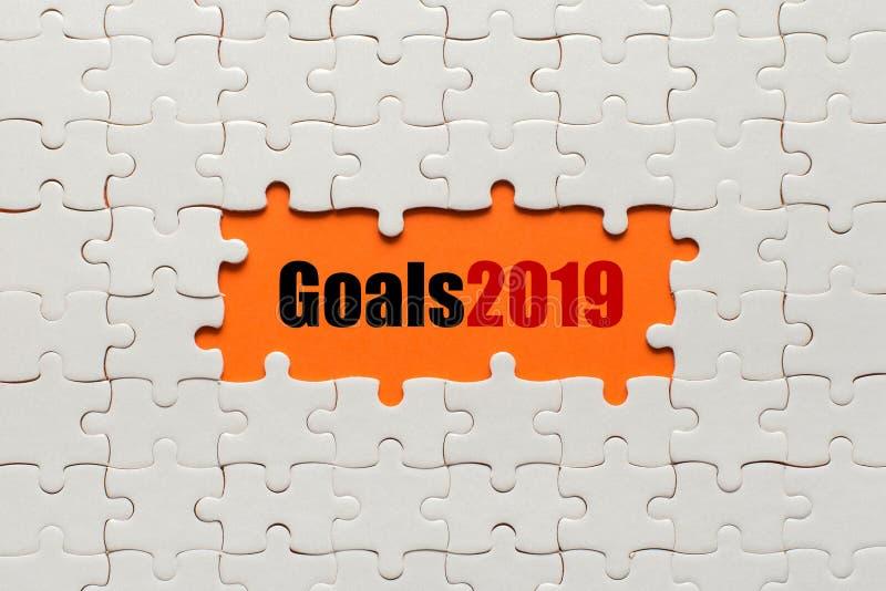 Doelstellingen 2019 Witte details van raadsel op oranje achtergrond stock fotografie