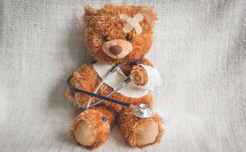 Doenças da infância do urso de peluche do conceito no fundo de matéria têxtil imagens de stock royalty free