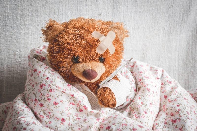 Doenças da infância do urso de peluche do conceito no fundo de matéria têxtil fotografia de stock