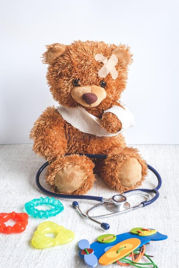 Doenças da infância do urso de peluche do conceito no fundo de matéria têxtil imagem de stock