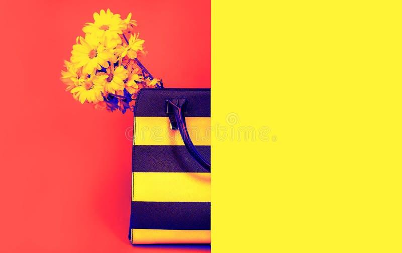 Doen de concepten in vrouwelijke toebehoren en gele bloemen op levendige neon rode kleur en gele achtergrond in zakken De uitrust royalty-vrije stock afbeeldingen