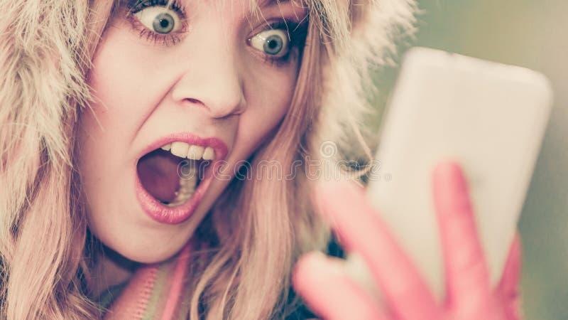Doen schrikken bange vrouw die op mobiele telefoon spreken stock foto