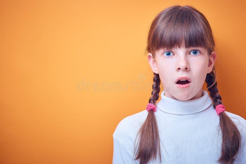 Doen schrikken en verrast Kaukasisch tienermeisje op gekleurde achtergrond, plaats voor tekst royalty-vrije stock fotografie