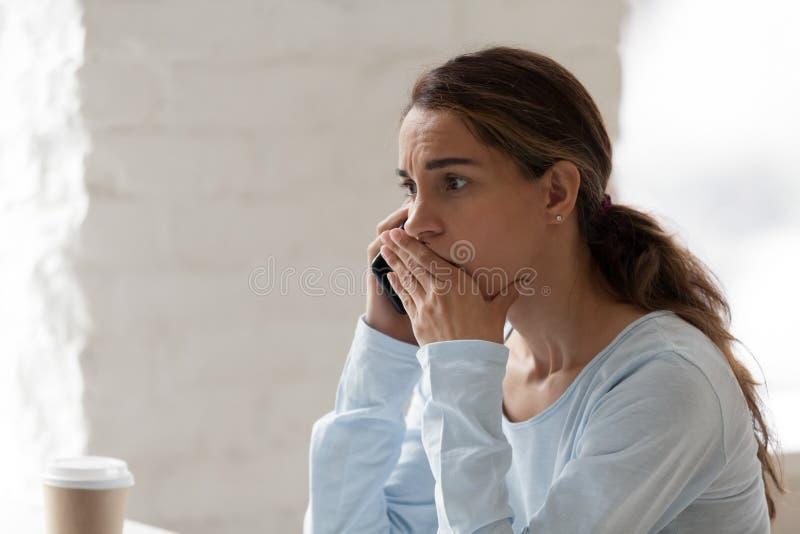Doen schrikken geschokte vrouw die op telefoon spreken, die slecht nieuws ontvangen royalty-vrije stock foto's