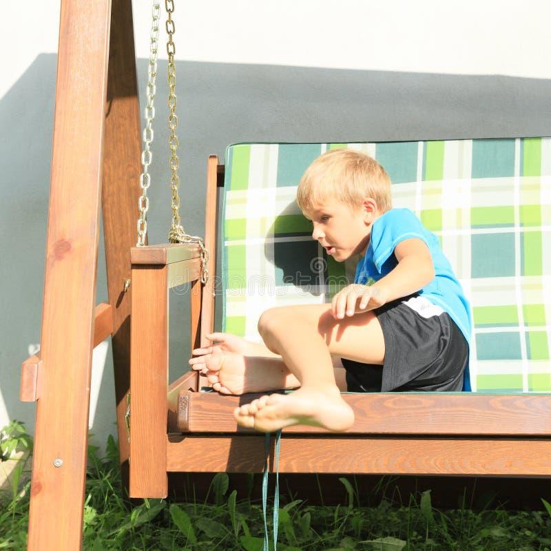 Doen schrikken jongenszitting op een houten schommeling stock afbeeldingen