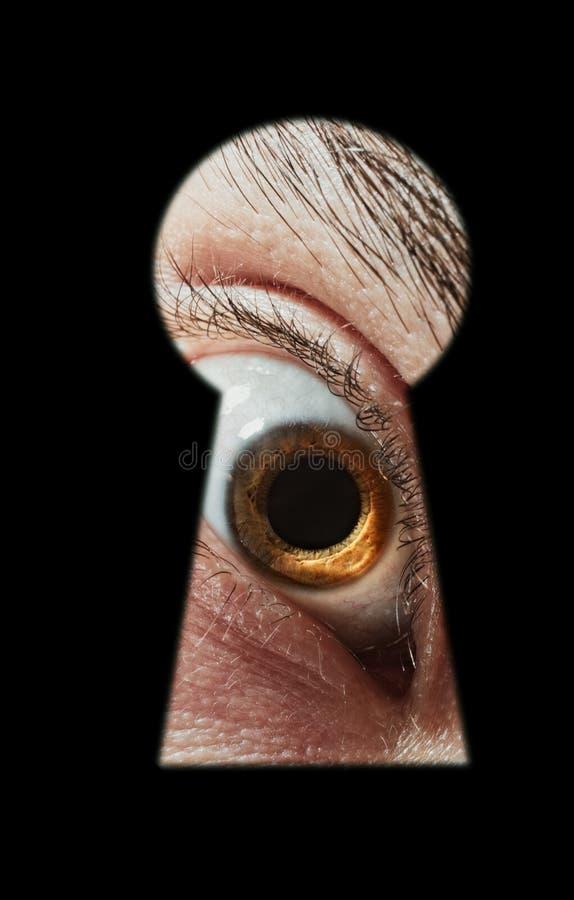 Doen schrikken mannelijk oog die door een sleutelgat spioneren stock afbeelding