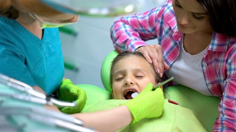 Doen schrikken meisje bezoekende tandarts, mamma die haar, regelmatige tandencontrole kalmeren stock afbeeldingen