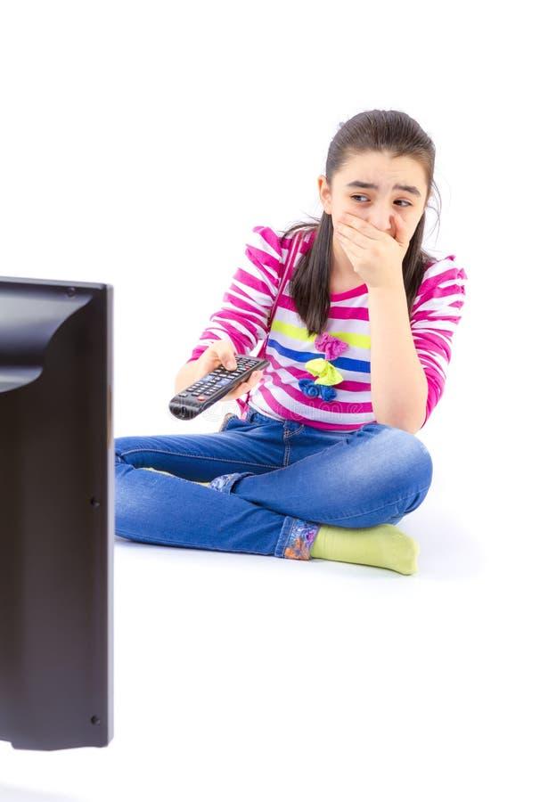 Doen schrikken meisje die op TV letten stock foto's