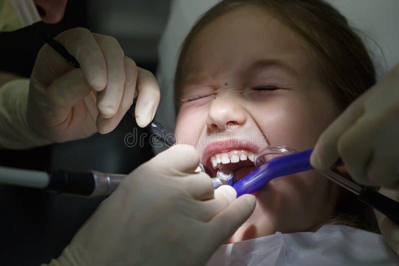Doen schrikken meisje op het tandartsenkantoor, in pijn tijdens een behandeling royalty-vrije stock fotografie