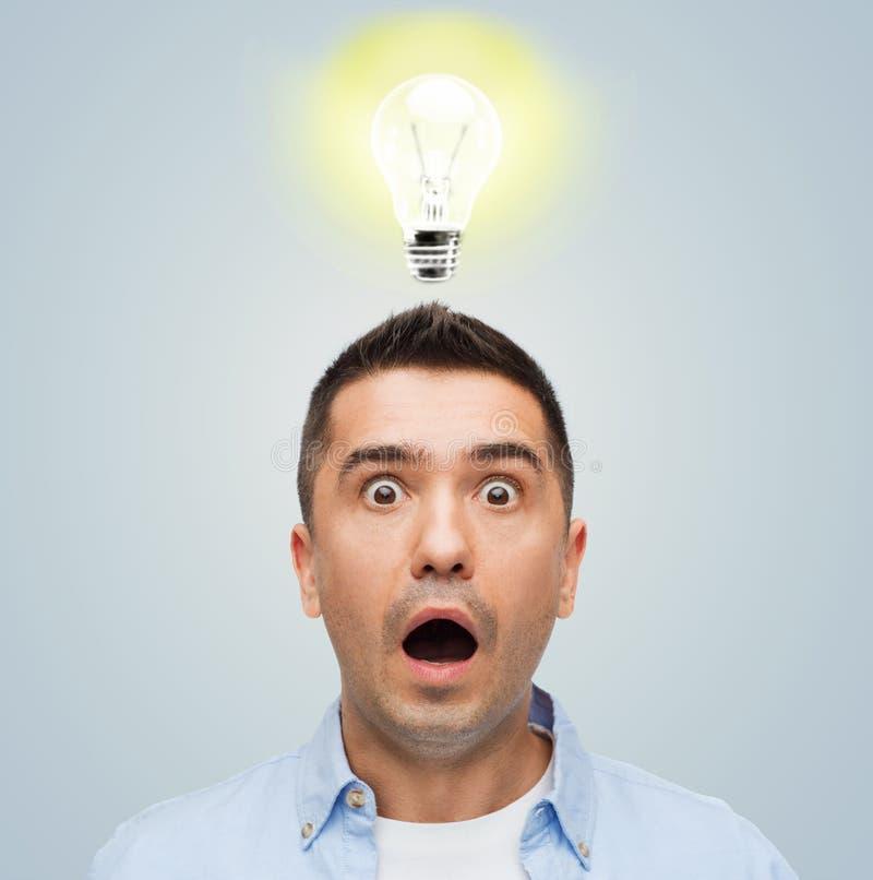 Doen schrikken mens die met verlichting boven zijn hoofd schreeuwen stock foto's