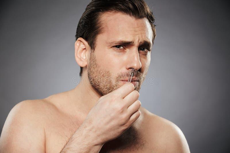 Doen schrikken mens die neushaar met pincet verwijderen stock foto