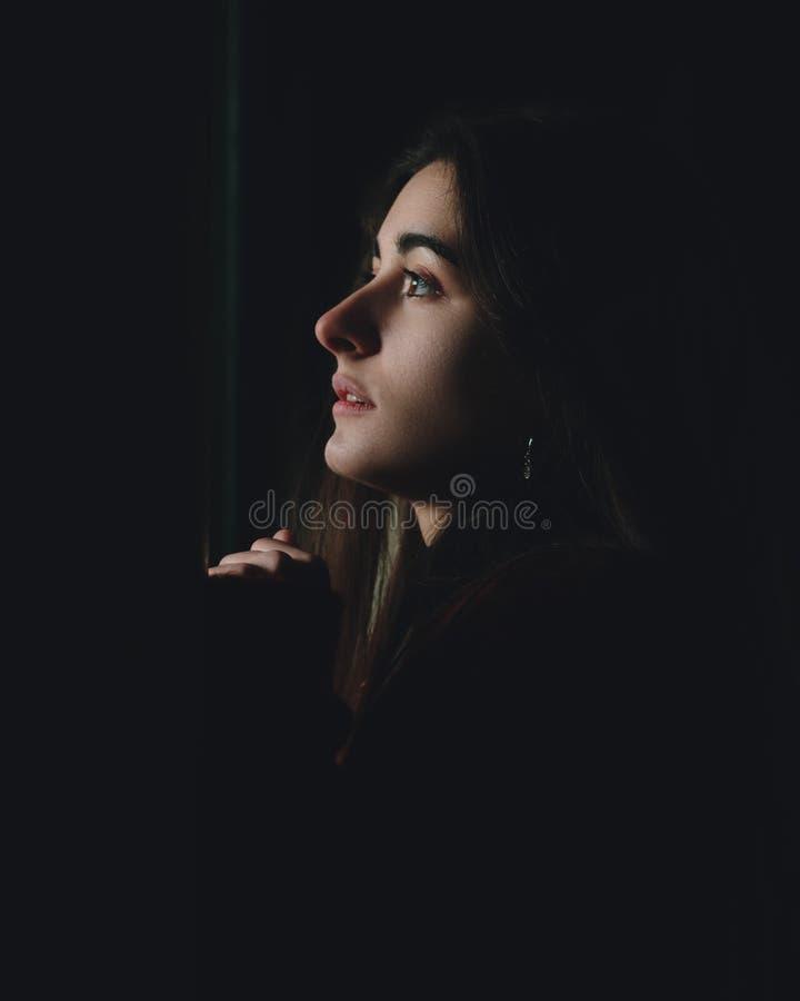Doen schrikken mooi vrouwenprofiel die omhoog in dark kijken Droevig tienergezicht gedeprimeerd het kijken door een venster in ee stock afbeeldingen