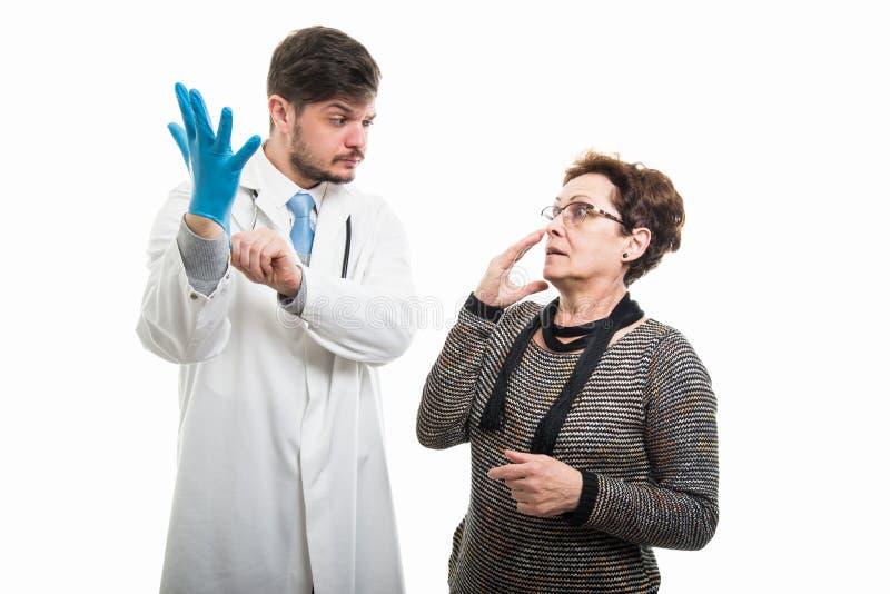 Doen schrikken vrouwelijke patiënt die aan verdachte mannelijke arts met glo kijken royalty-vrije stock afbeeldingen