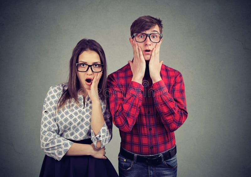 Doen schrikken zenuwachtige man en vrouw die met wijd geopende mond camera bekijken royalty-vrije stock afbeelding