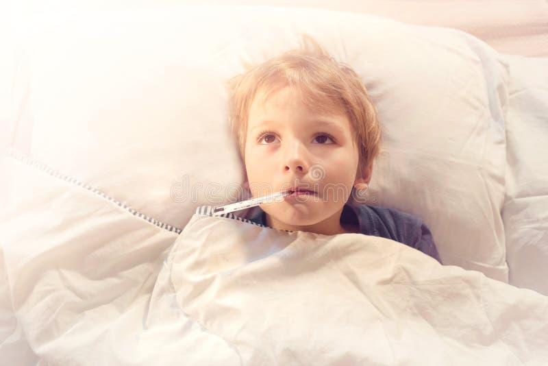 Doente da criança na cama com febre e termômetro foto de stock royalty free