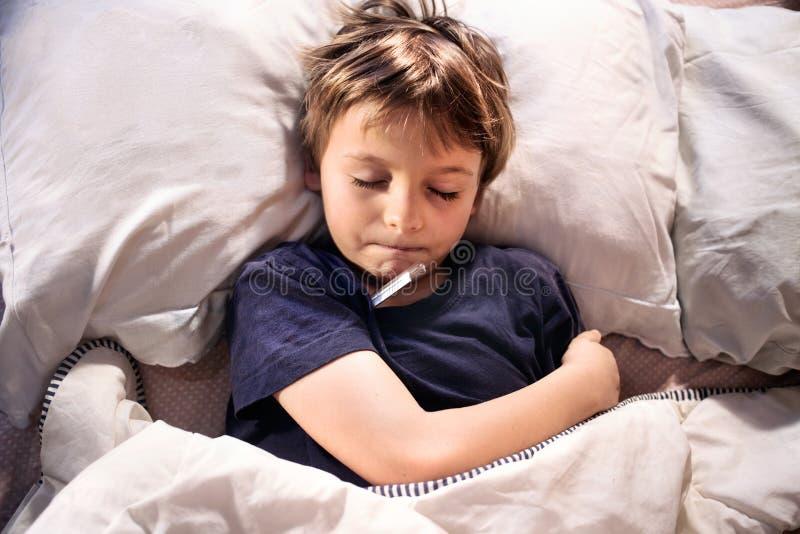 Doente da criança na febre de sono e de teste da cama fotografia de stock