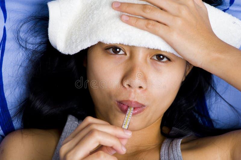 Doente da mulher consideravelmente nova na cama fotografia de stock royalty free