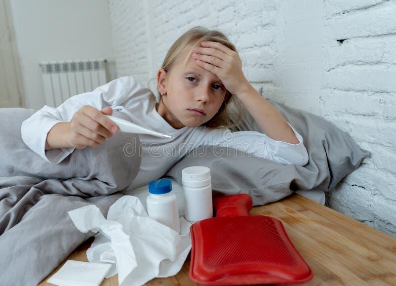 Doente de encontro da menina no sentimento da cama doente com febre alta e na dor de cabeça que está com uma gripe fria imagens de stock royalty free