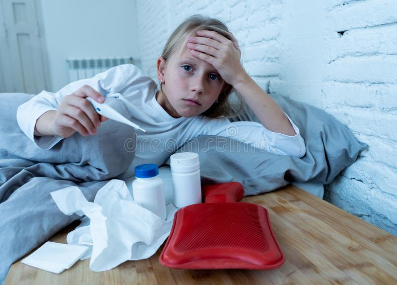 Doente de encontro da menina no sentimento da cama doente com febre alta e na dor de cabeça que está com uma gripe fria fotografia de stock