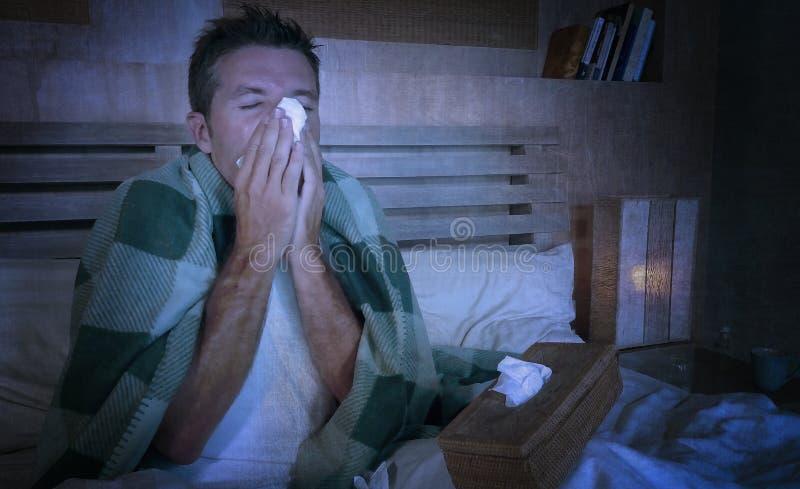 Doente desperdiçado do homem em casa que congela-se na cama coberta com a cobertura que aspira o grippe de sofrimento do nariz es imagem de stock