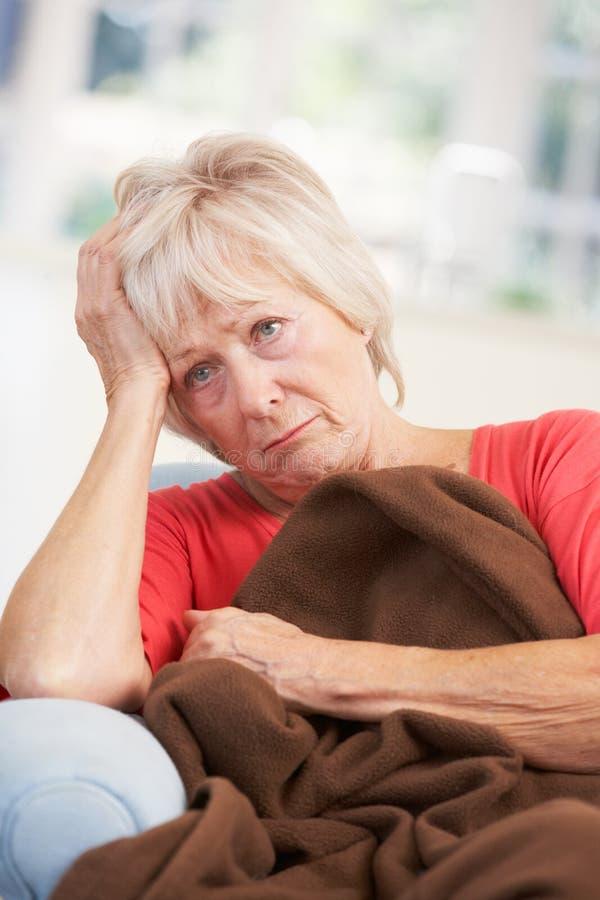 Doente, mulher mais idosa infeliz em casa imagem de stock