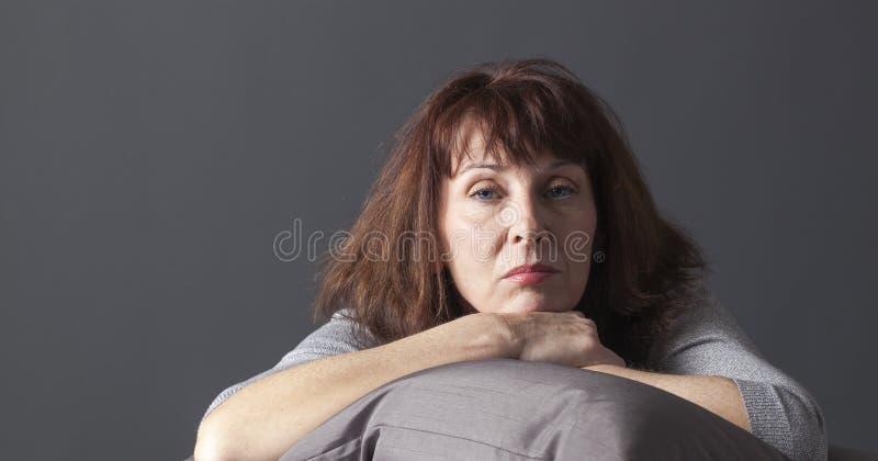 Doente superior de relaxamento da mulher de ter azuis da menopausa imagem de stock