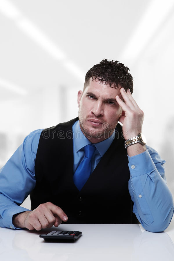 Does it add up. Business man working at his desk adding up doing sums royalty free stock photography
