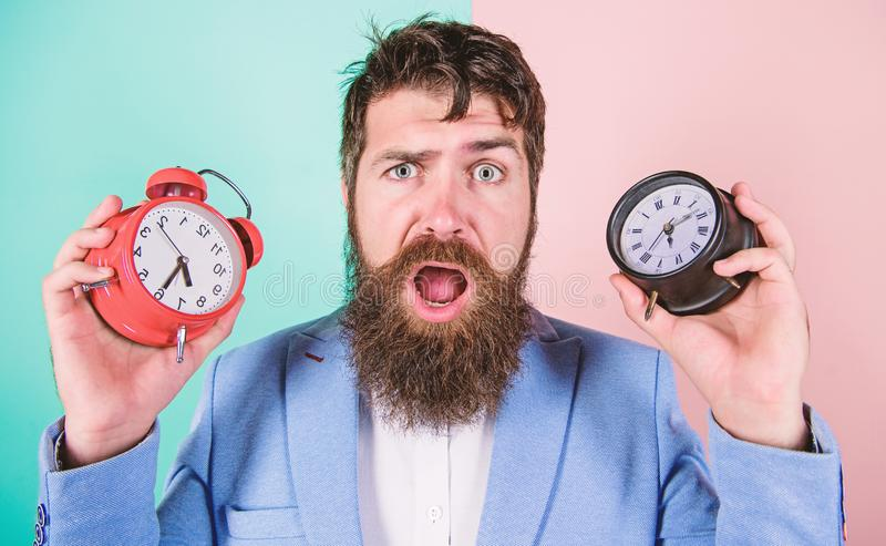Does changing clock mess with your health. Man bearded hipster hold two different clocks. Guy unshaven puzzled face stock photo