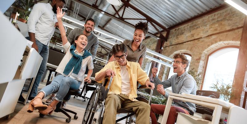 Does work make you happy. Young positive asian man in wheelchair having fun with his colleagues at modern office royalty free stock image