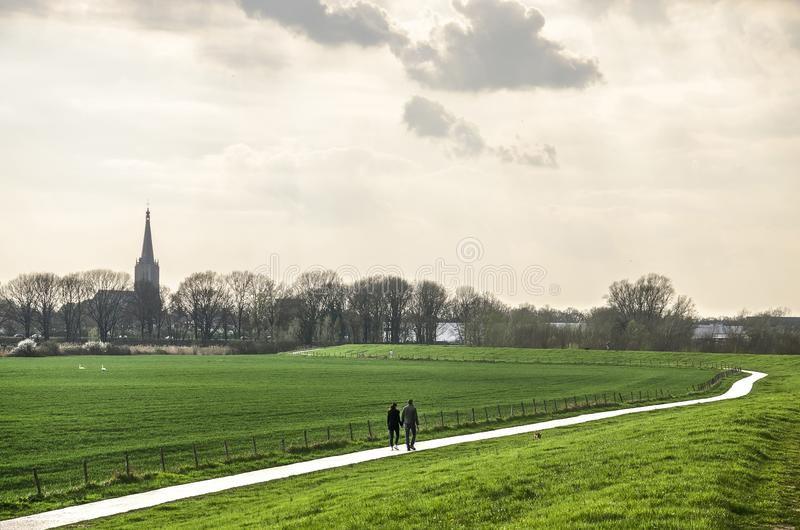 The road to Doesburg. Doesburg, The Netherlands, March 30, 2019: two people walking on a path along the dike towards town under a dramatic sky royalty free stock image