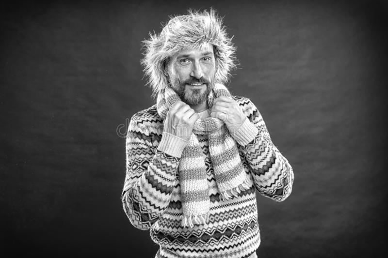 He doesnt want to freeze. Bearded man accessorizing sweater with hat and scarf. A winter set protects him from cold. Winter male outfit. Mature fashion model royalty free stock photography