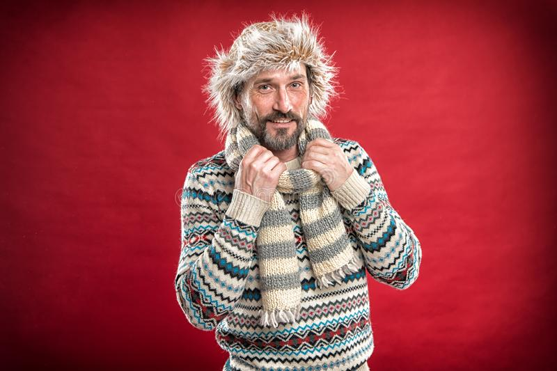 He doesnt want to freeze. Bearded man accessorizing sweater with hat and scarf. A winter set protects him from cold. Winter male outfit. Mature fashion model royalty free stock photos