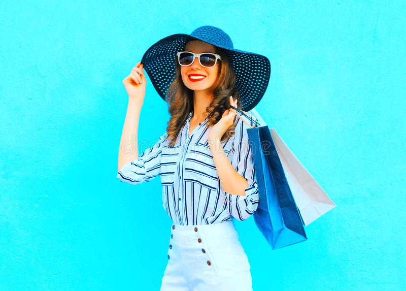 Doet de manier jonge glimlachende vrouw die het winkelen dragen, strohoed in zakken royalty-vrije stock foto