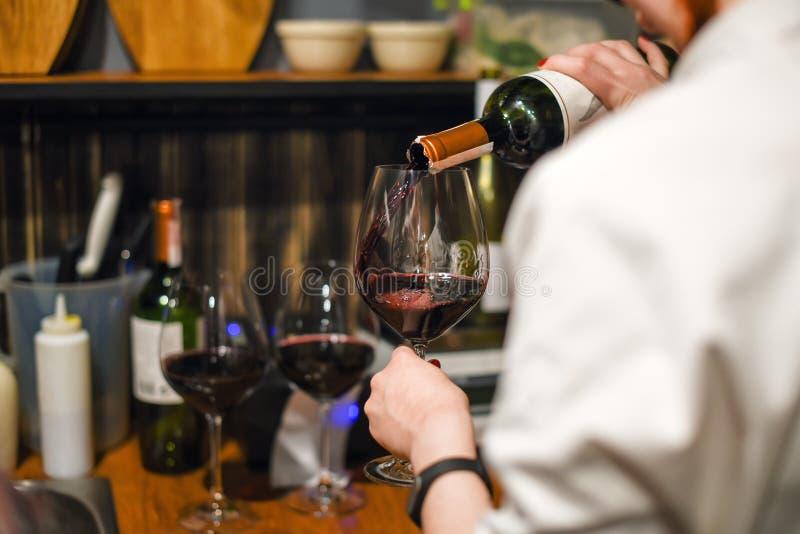 dof отмелое вино кельнера Умелый сомелье лить красное вино в стекло Женщина держа бутылку и рюмку стоя внутри стоковое фото rf