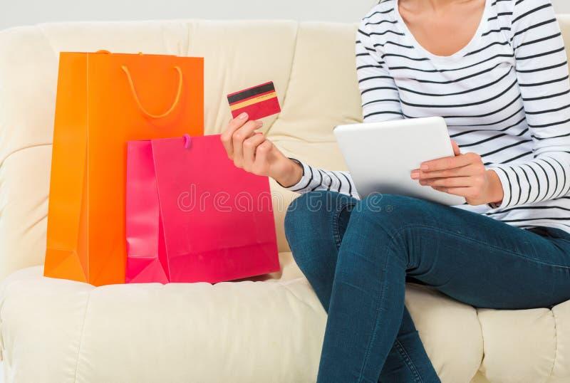 dof ręce karty ogniska płytki zakupy online bardzo uśmiechnięta młoda kobieta z pastylką i kredytową kartą fotografia stock