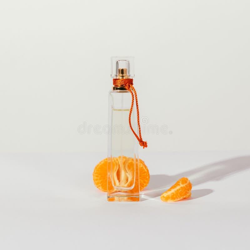 Doft i genomskinlig flaska och halva av den skalade tangerin royaltyfria foton