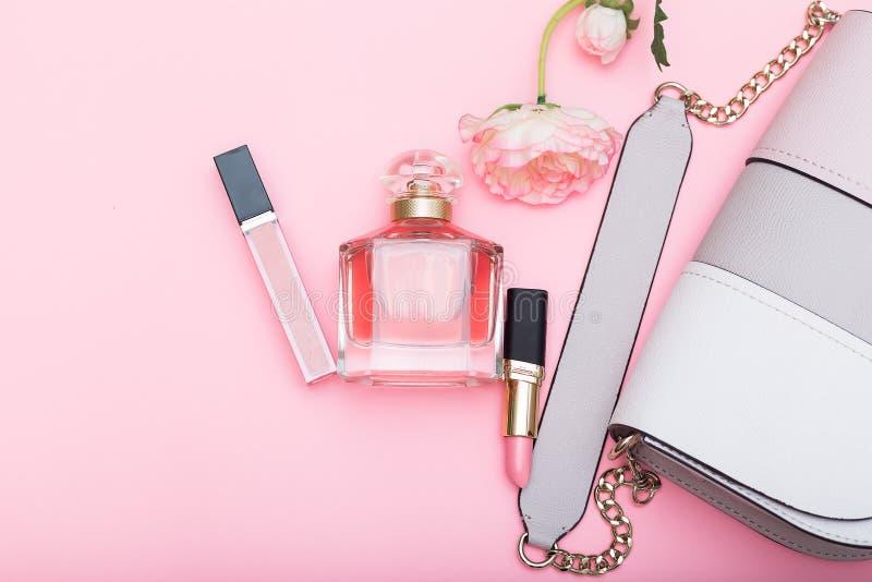 Doft, kantglans, läppstift och påse på en rosa bakgrund arkivbilder