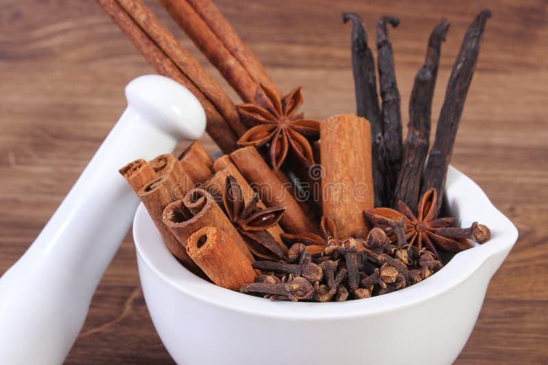 Doftande anis-, kryddnejlika-, kanel- och vaniljpinnar i mortel på lantligt bräde arkivbilder