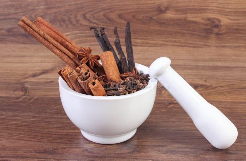 Doftande anis-, kryddnejlika-, kanel- och vaniljpinnar i mortel på lantligt bräde arkivbild