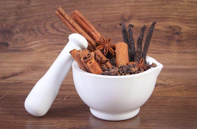 Doftande anis-, kryddnejlika-, kanel- och vaniljpinnar i mortel på lantligt bräde royaltyfri foto