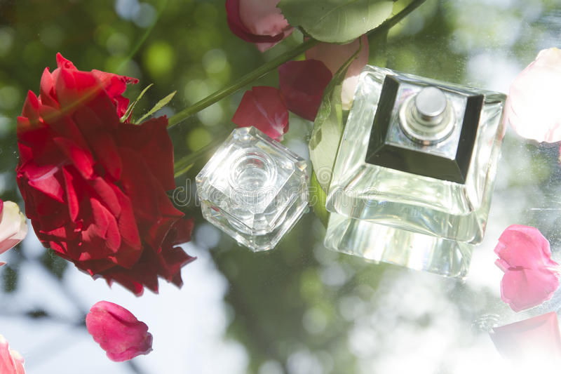 Doftflaska i natur med Rose Petals royaltyfria foton