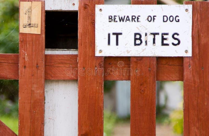 Dog bites sign. On a garden gate stock image